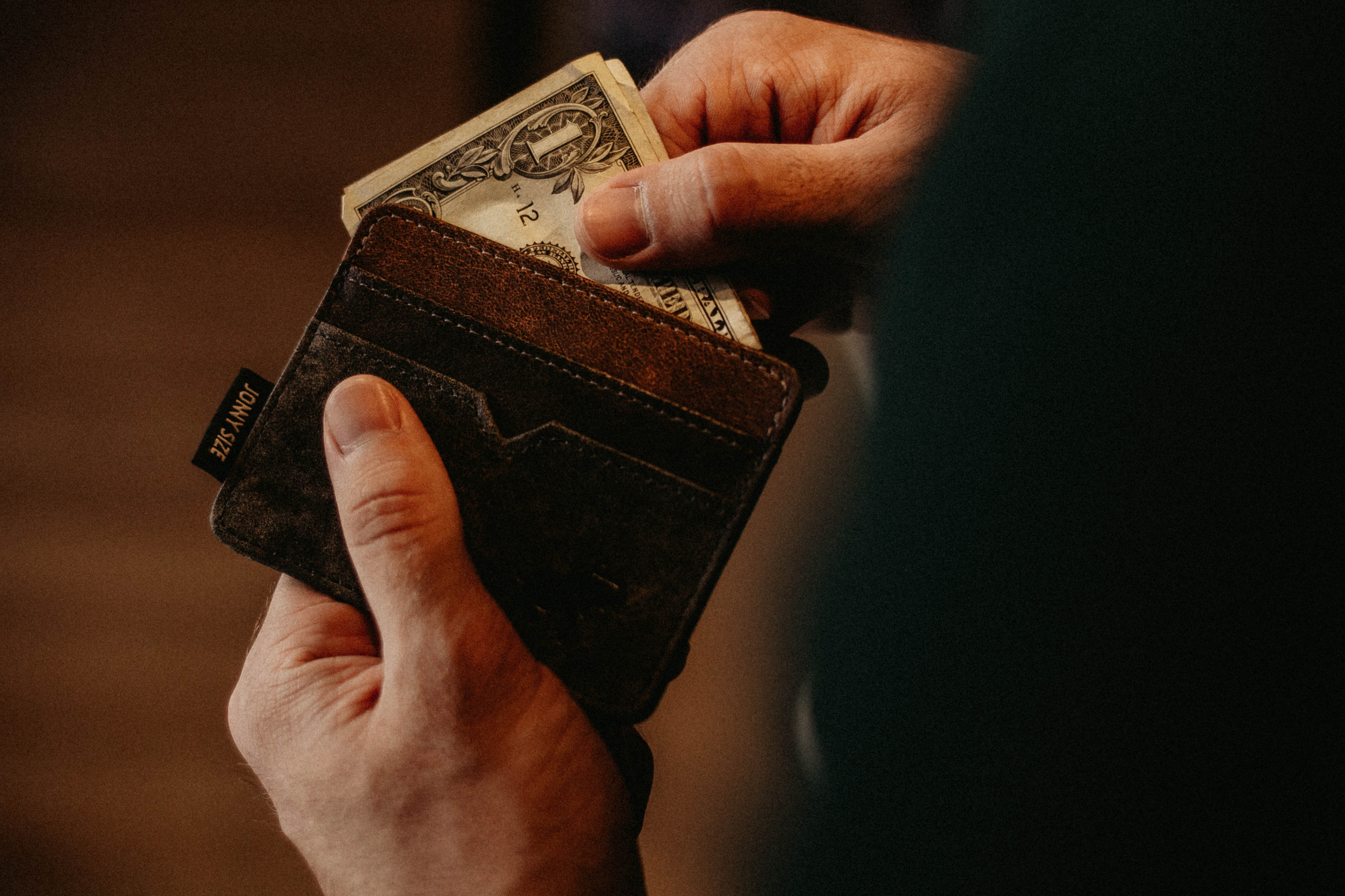 A man pulling out a dollar bill out of his brown wallet, ready to pay for storage Brooklyn.