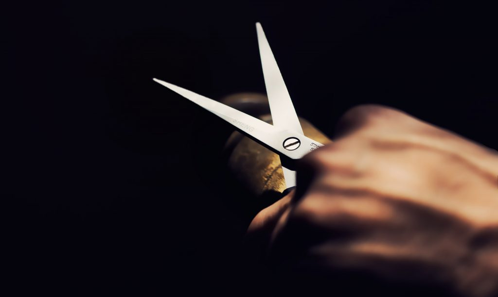 A hand holding a pair of scissors on a dark background. - pack your valuable items properly