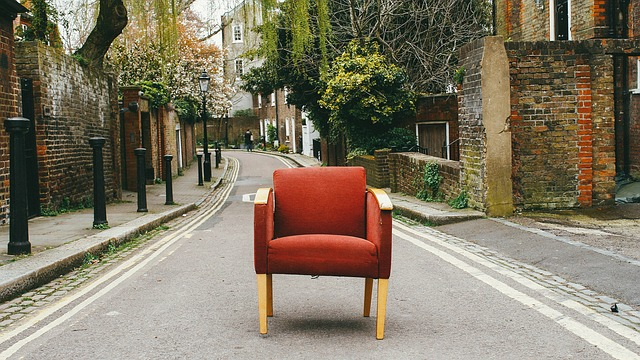 An old armchair standing in the middle of the street.