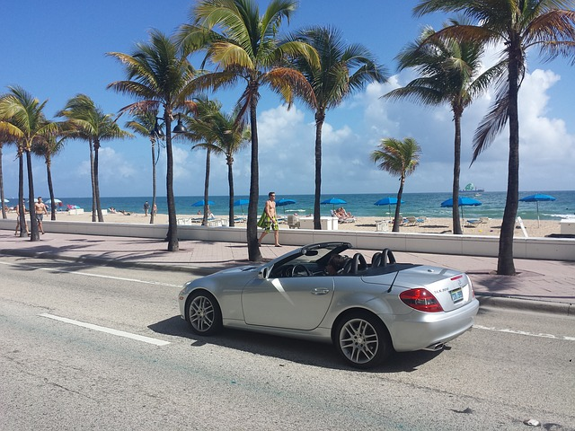 A convertible parked in front of a Miami beach.