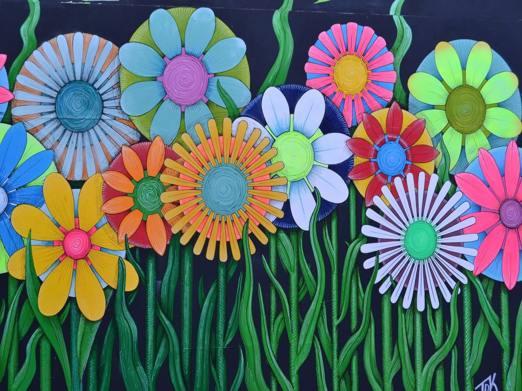 A wall painting of tall colorful flowers.
