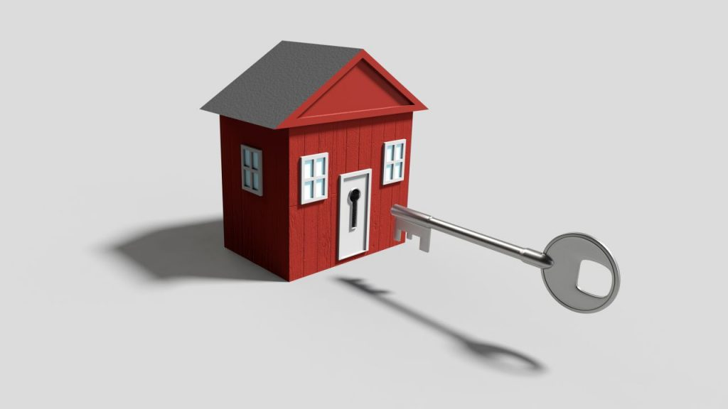 A computer generated image of a small red house with a giant key.