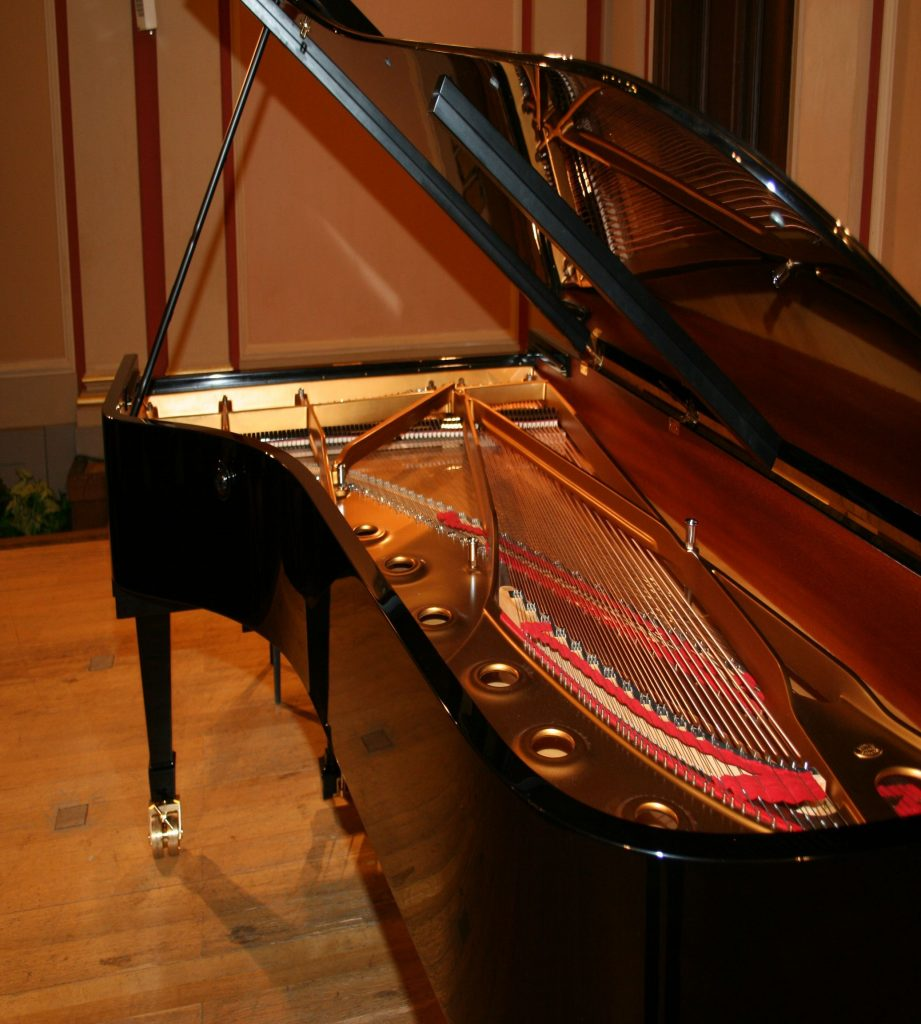 A brown piano with the main lid lifted up, moved by piano movers.