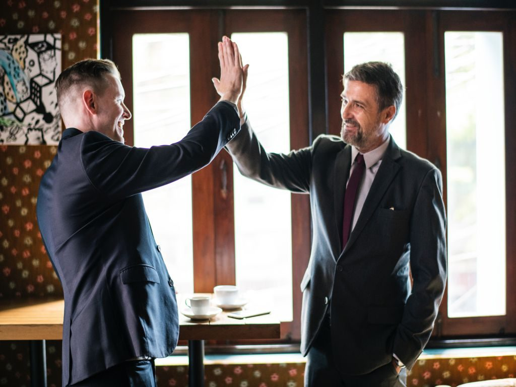 Two businessmen high-fiving each other.