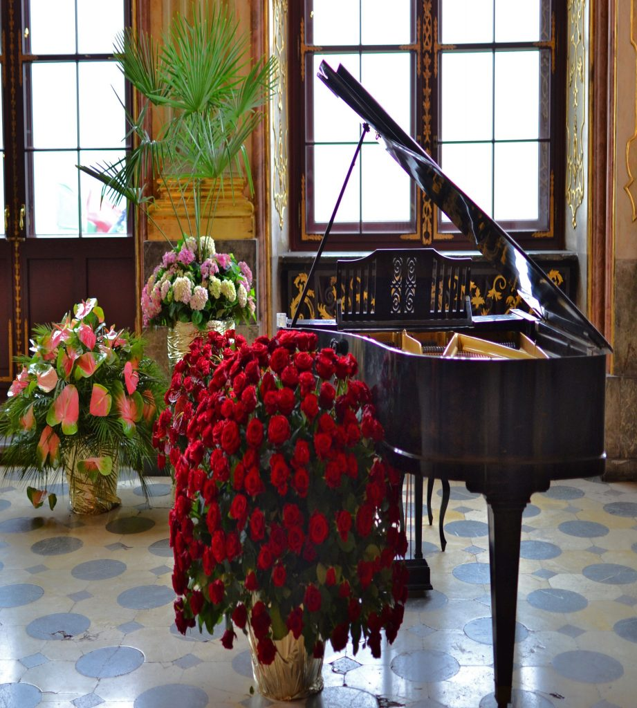 A piano surrounded by bouquets of flowers.
