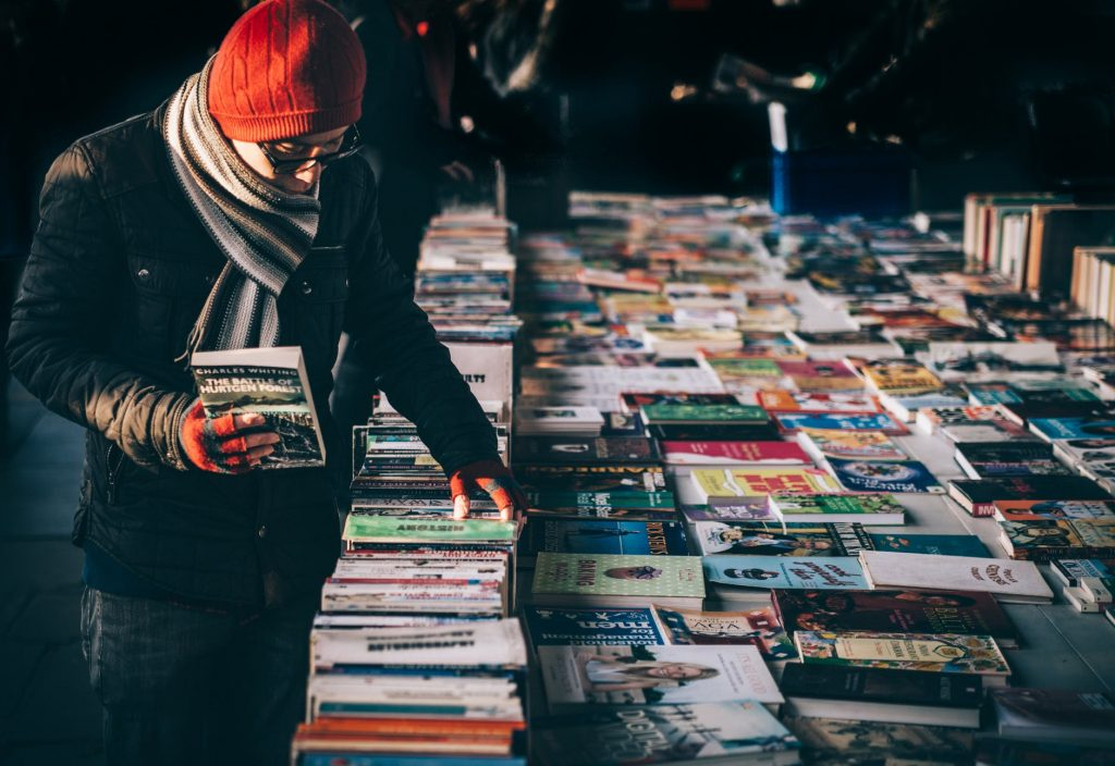 A man in front of a stand with books.