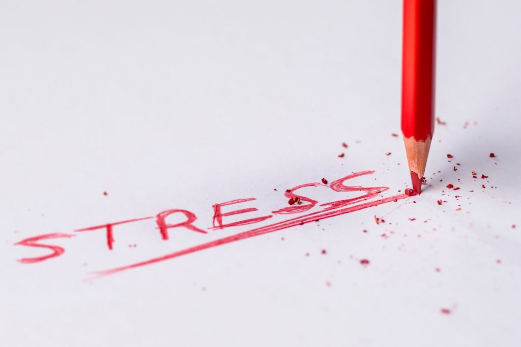 The word stress written on a white paper with a red pen.