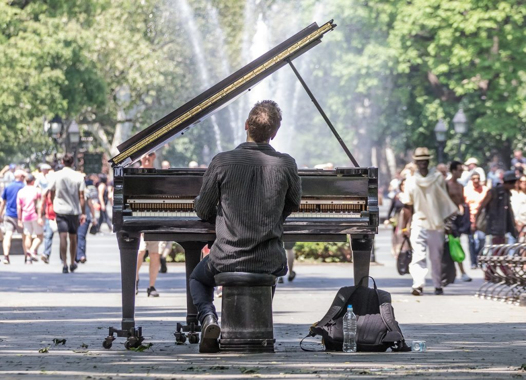 A man playing a piano directly on the street. Maybe he'll be a headliner of popular music festivals in NYC a few years from now.