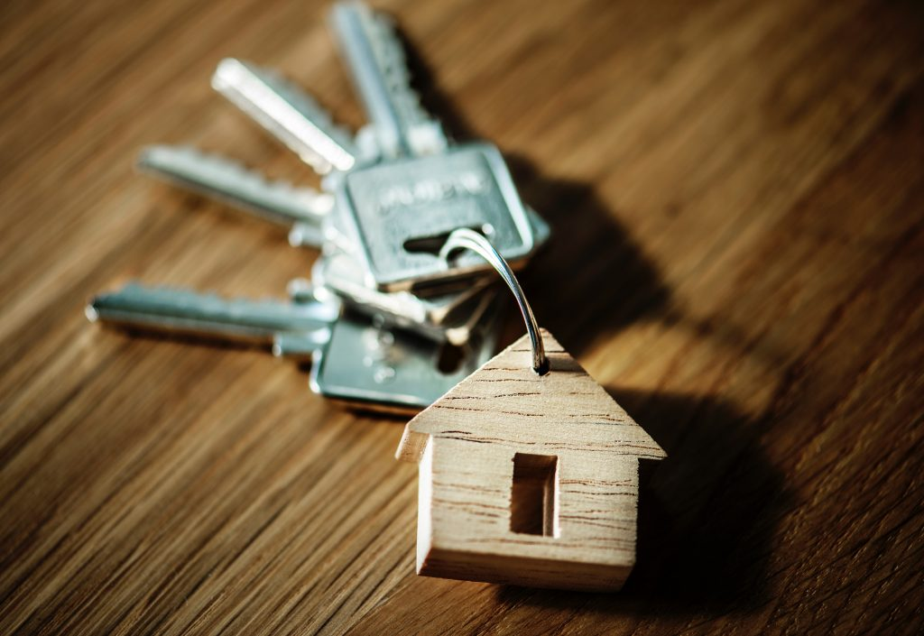 A set of keys with a key-ring in the shape of a house.