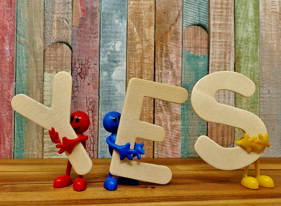 The word yes held by figurines.