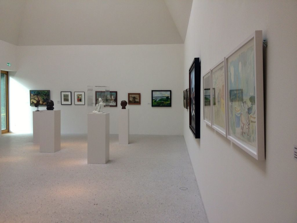 A gallery exhibit with paintings and other pieces.