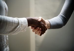 Two people shaking hands in agreement about a museum job in NYC.