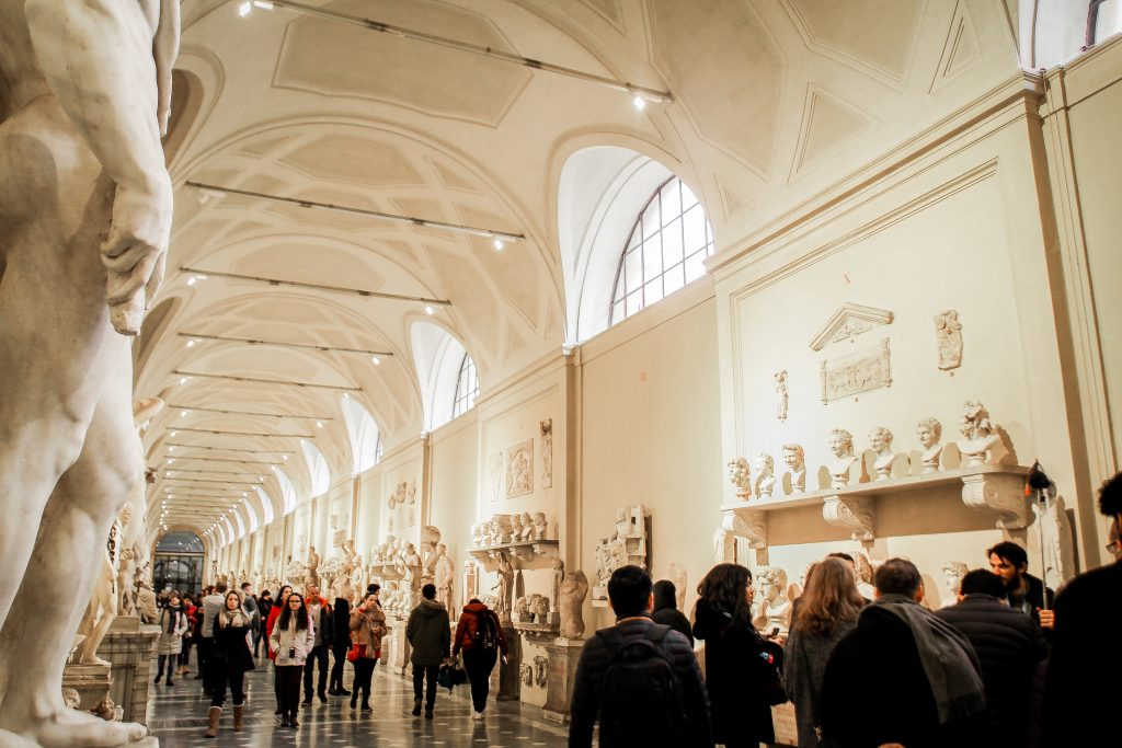 A museum full of visitors looking around.