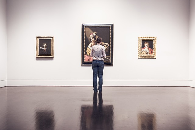 A woman in a gallery looking at paintings.