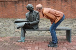A statue of a man with a newspaper on a bench. A human man is looking in his face.