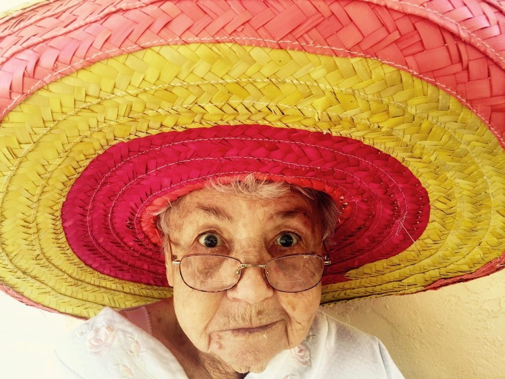 A grandma in a sombrero, enjoying in one of the NYC neighborhoods for retirees.