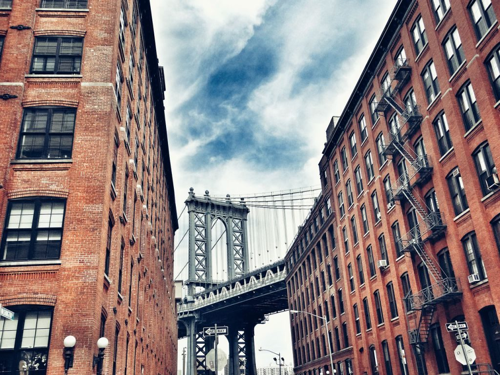 Two red brick apartment buildings, with the Brooklyn Bridge in the middle, seen after moving to Crown Heights.