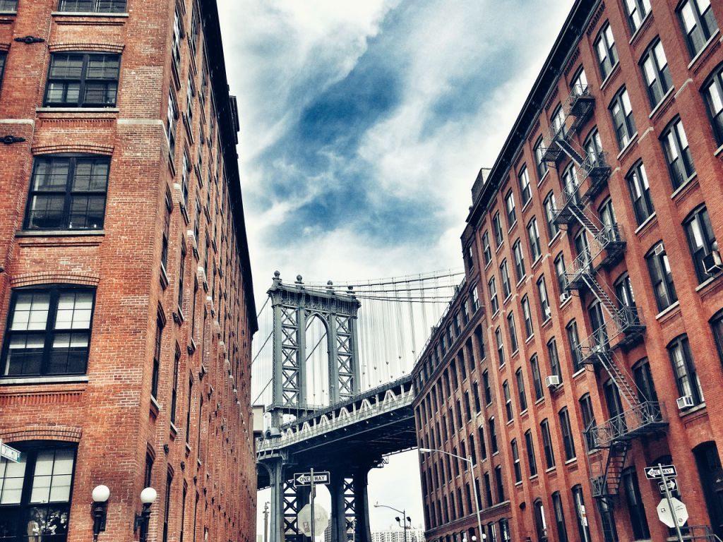Twee rode bakstenen flatgebouwen, met de Brooklyn Bridge in het midden, gezien na de verhuizing naar Crown Heights.
