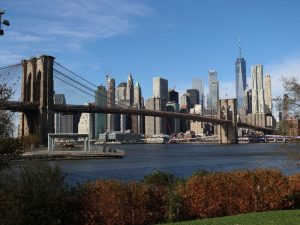 A view of the NYC skyline with the Brooklyn Bridge in the forefront.