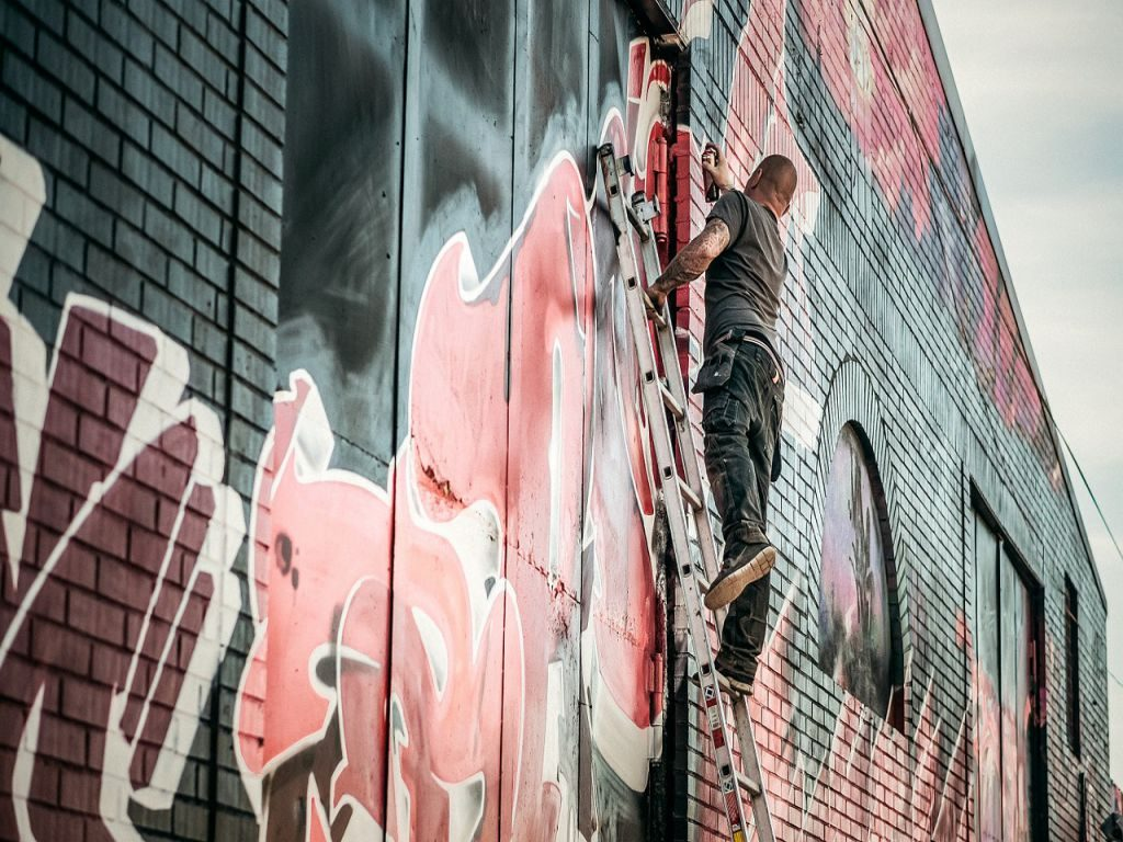 A man on a ladder working on street art on an exterior brick wall.