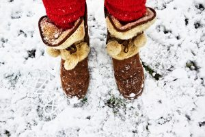 A person wearing snow boots standing in the snow.