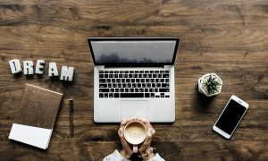 """A laptop, a coffee cup, a phone, a potted plant, and a notebook. Letters spelling out """"DREAM"""" are artistically to the side. Starting a business in Prospect Heights is a great way to turn your dream into a reality!"""