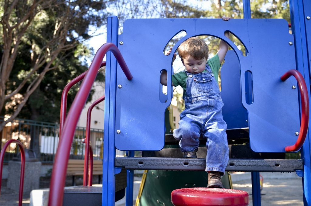 A child is playing on a climbing structure on a playground.