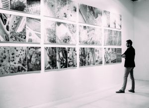A black and white photography of a man looking at a gallery of sharply arranged abstract art. He looks pensive.