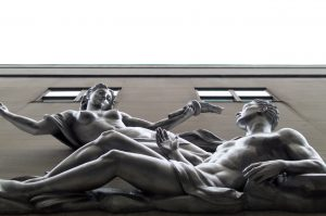 A statue of a man and a woman lounging in front of building windows.