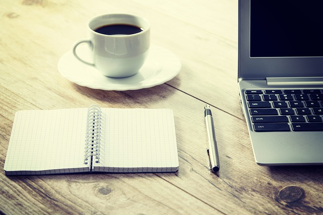 Laptop, Coffee Cup and a Notebook on a Wooden Desk