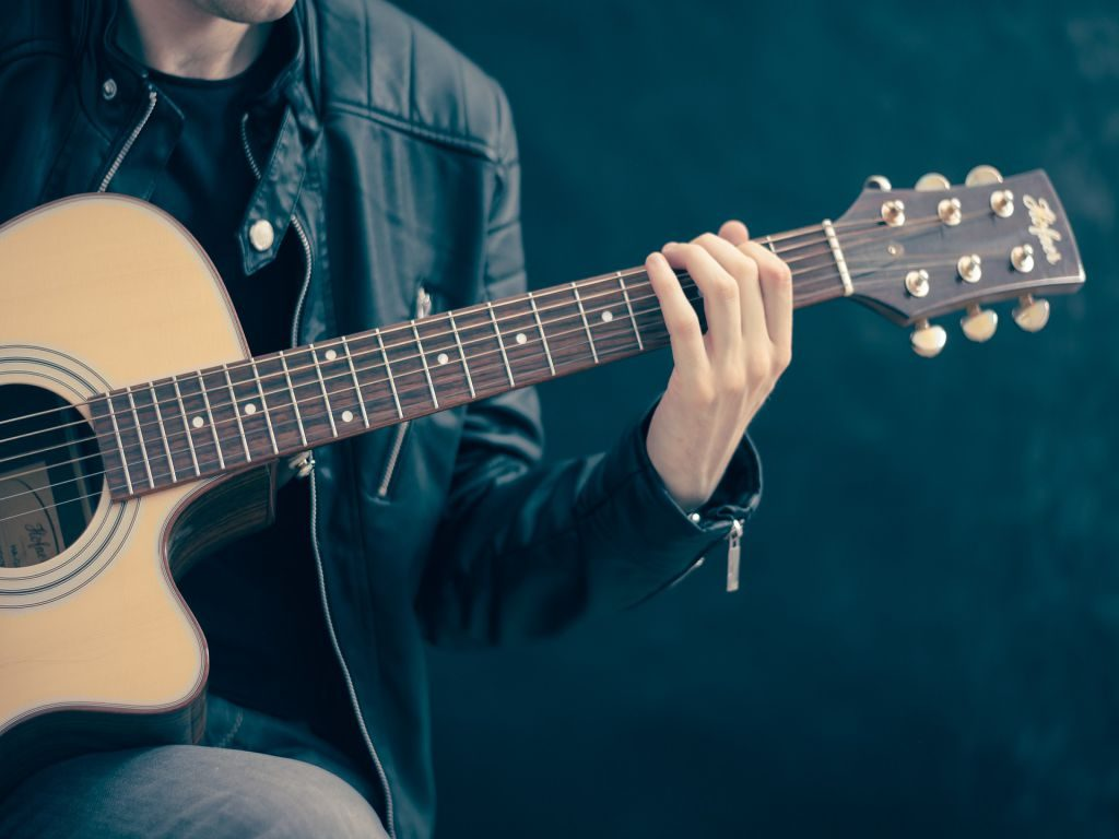 A man playing guitar against a black background.