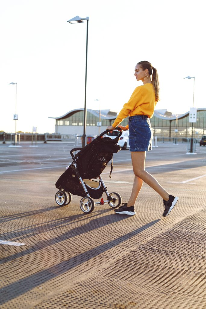 A fashionable young mom pushing a stroller after moving to Park Slope. She's wearing a denim skirt, a yellow jacket, and her hair is in a pony tail.
