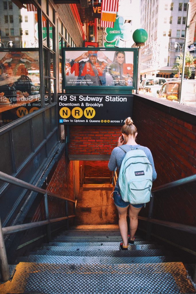 A woman descending into the subway.