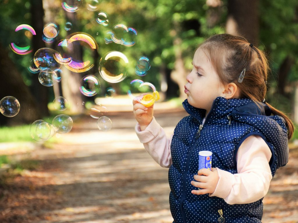 A little girl blowing bubbles outdoors - if you're moving to a warmer climate , this can be your kid!