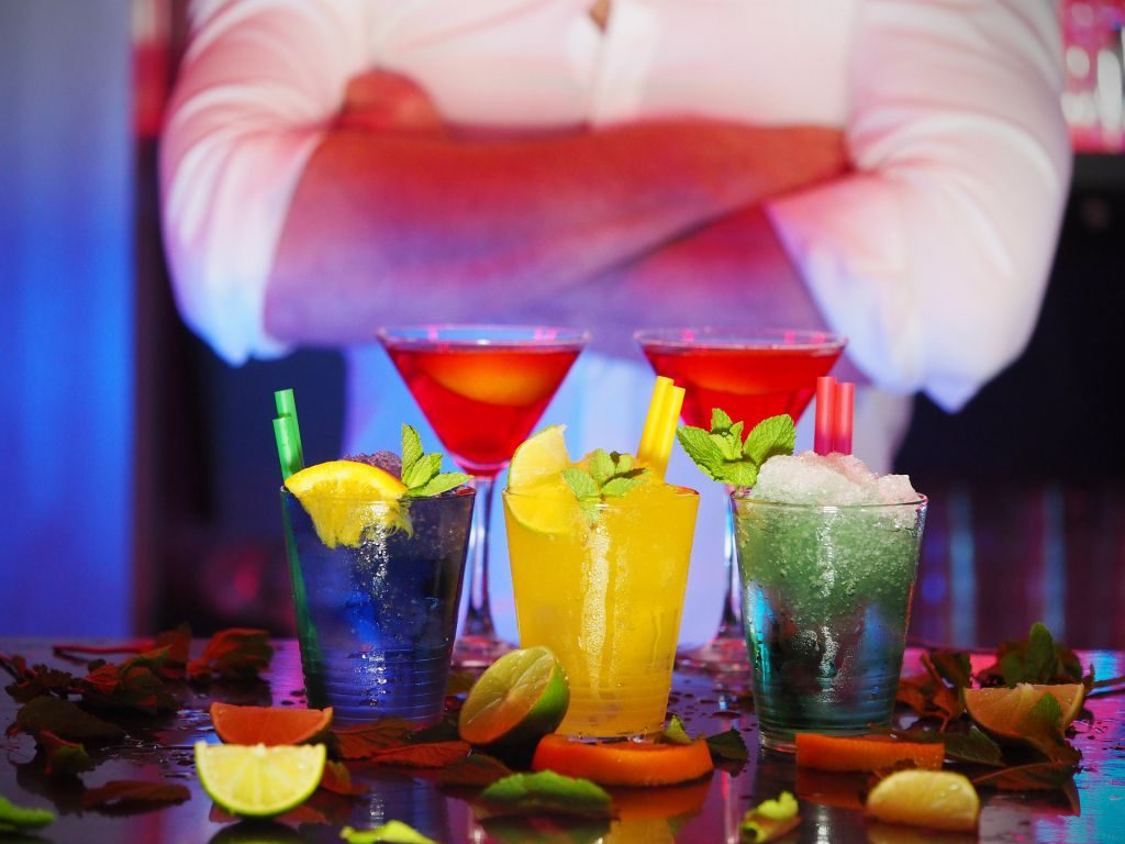 A bartender standing behind a row of colorful cocktails.