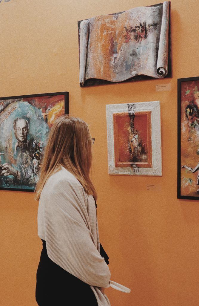 A woman looking at a piece of art. The wall is orange, and so is most of the art.