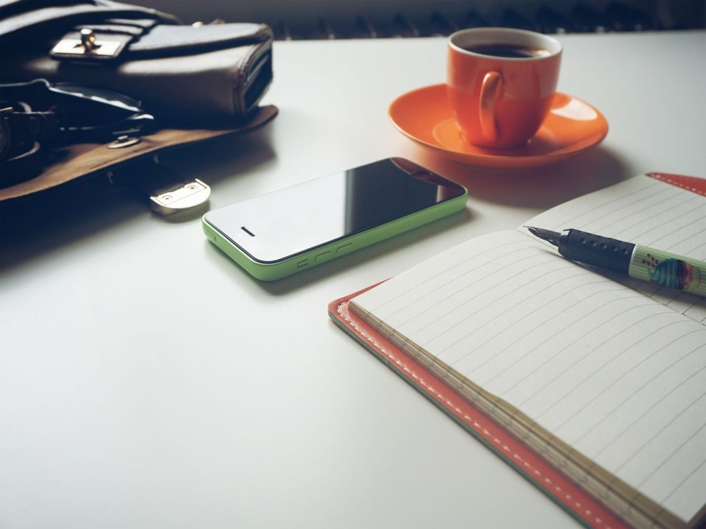 A notebook next to a phone and a cup of coffee.