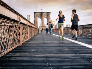 A bunch of people jogging on the Brooklyn Bridge. They're wearing skimpy outfits.