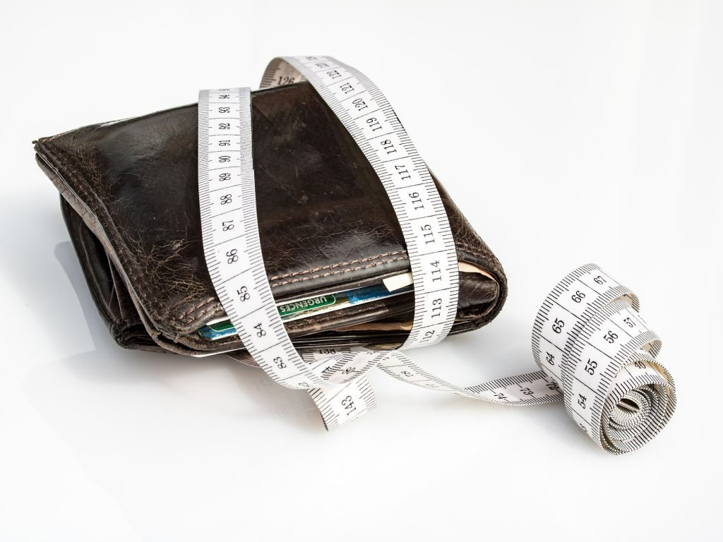 A wallet with measuring tape on a white surface.