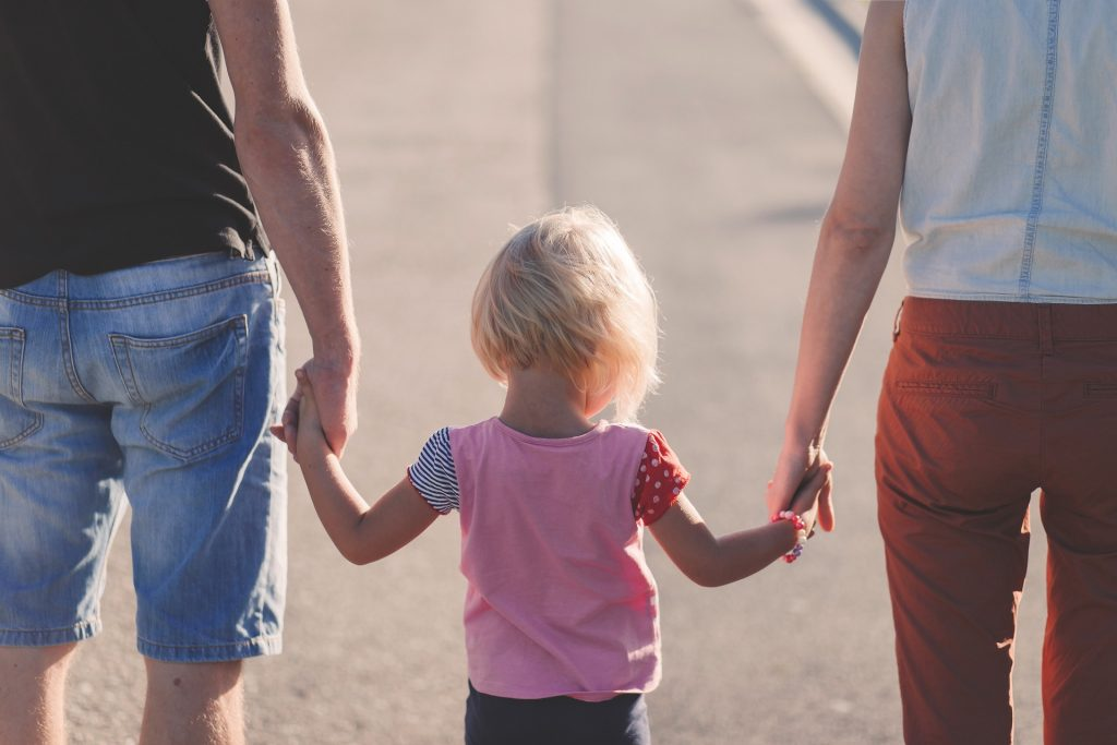 A small blonde toddler holding hands with their parents.