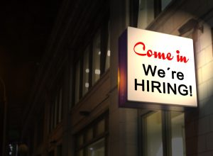 "A glowing sign that says ""Come in, we're HIRING!""."