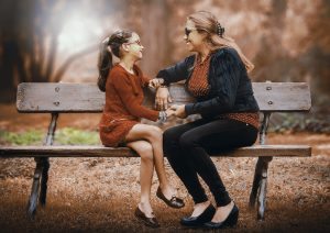 A mother and a daughter chilling on a bench.