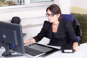 A white woman dressed sharply and professionally, sitting behind a desk and looking at a laptop. She looks determined and concentrated. She's wearing glasses.