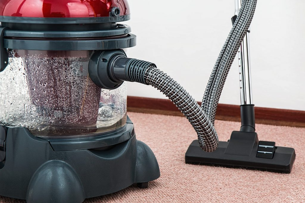 A vacuum cleaner. It's a shiny maroon cover, with black plastic. When you pack your appliances for relocation, make sure you don't forget the vacuum.