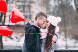 A couple hugging, girl holding heart balloons, wintertime