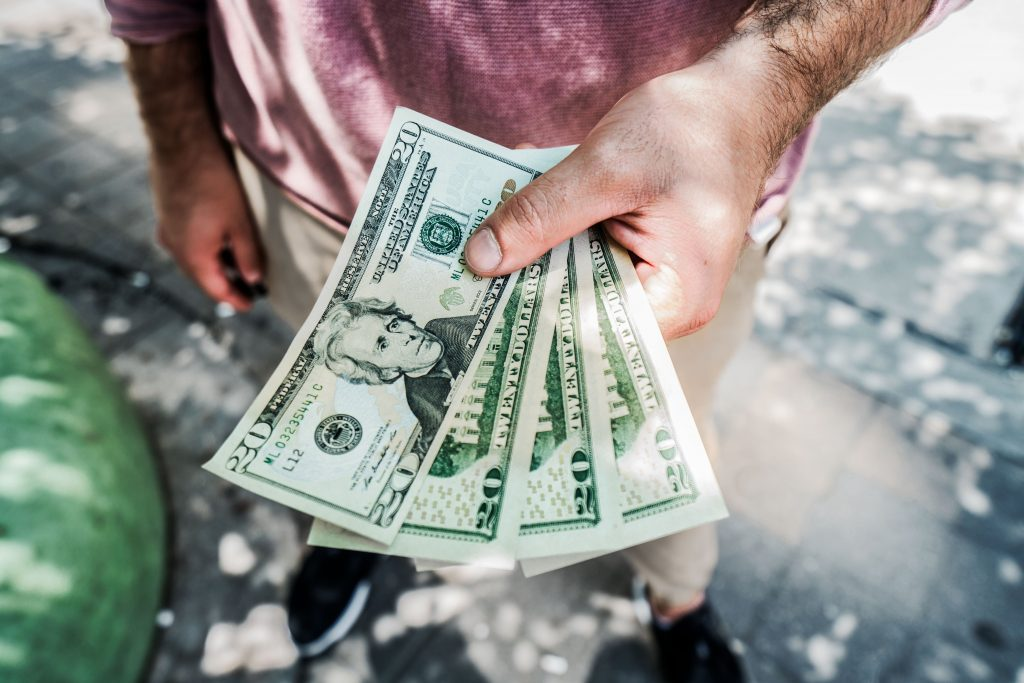 a person holding dollars in his hand