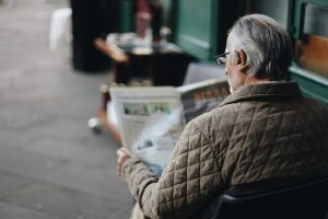 Elderly man reading a newspaper