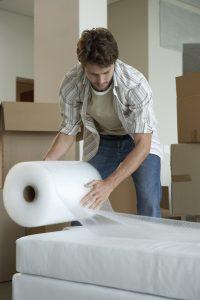 Man wrapping furniture