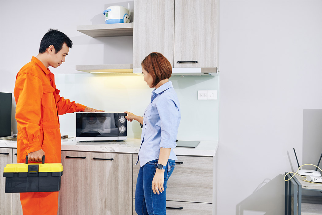 A Repairman And A Woman Are Looking At A Microwave